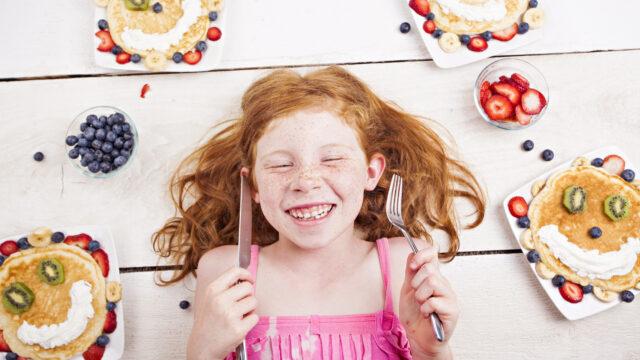 パンケーキに囲まれる幸せそうな少女